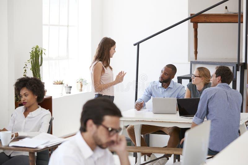 Collega's in bespreking rond een bureau in open planbureau stock fotografie