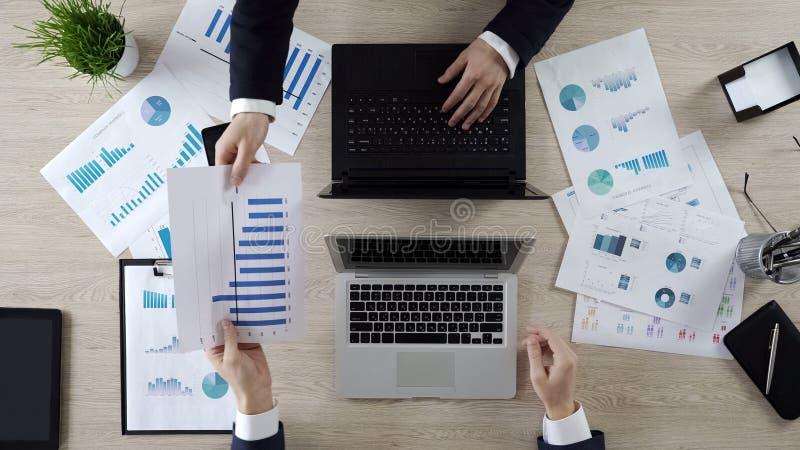 Collega's die aan bedrijfsproject werken, die bedrijfstatistieken, hoogste mening bespreken stock fotografie
