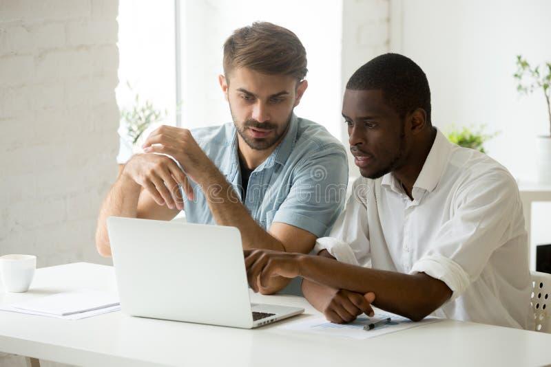 Collega's die bedrijfskwesties bespreken, die bij laptop werken royalty-vrije stock afbeelding