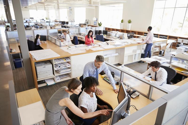 Collega's die bij het werkstation van een vrouw in een bezig bureau werken stock foto's