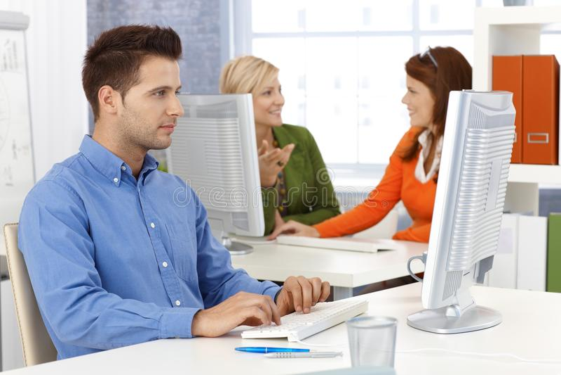 Collega's die in bureau werken stock afbeeldingen