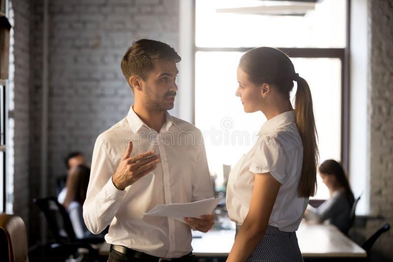 Collega's die delend informatie en gedachten tijdens werkdag spreken stock foto