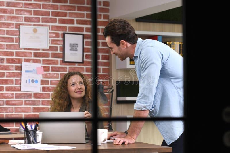 Collega's die het werk bespreken die laptop in het bureau met behulp van stock afbeelding