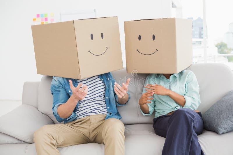 Collega's die hun hoofd behandelen met de doos van het pretkarton stock foto's
