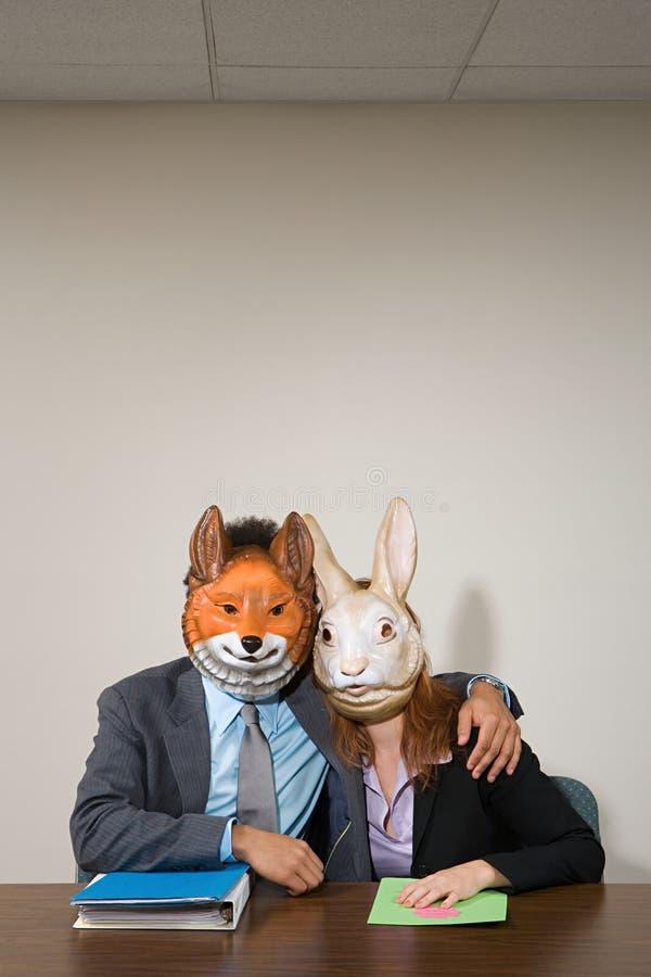 Collega's die maskers dragen royalty-vrije stock afbeelding