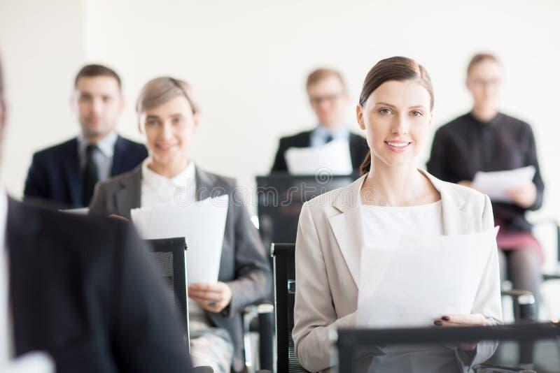 Collega's die met documenten op overeenkomst zitten stock foto