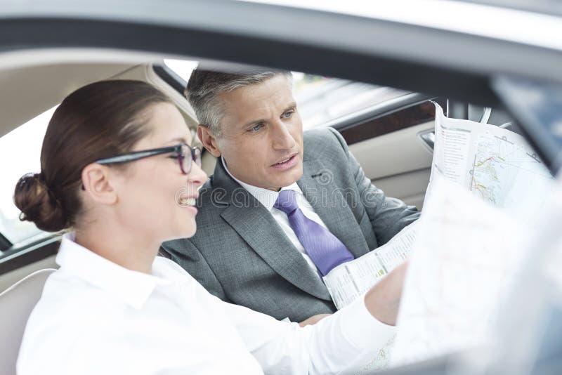 Collega's die over kaart in auto bespreken royalty-vrije stock afbeeldingen