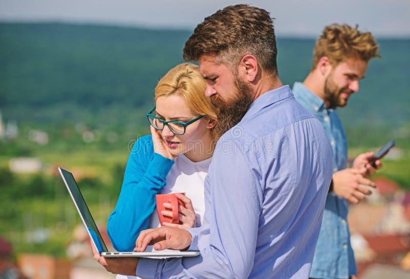 Collega'spartners die met laptop en smartphone voordelen van het mobiele Internet-openlucht werken nemen collega's stock afbeeldingen