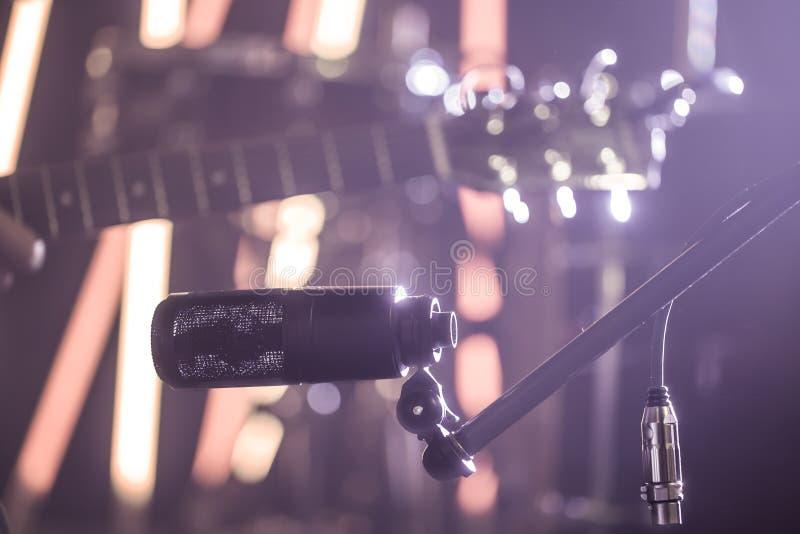 Collegamenti del microfono per il primo piano di registrazione della chitarra acustica, in uno studio di registrazione o in una s immagini stock