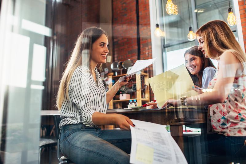 College female students sitting at table working on school assignment in a library royalty free stock image