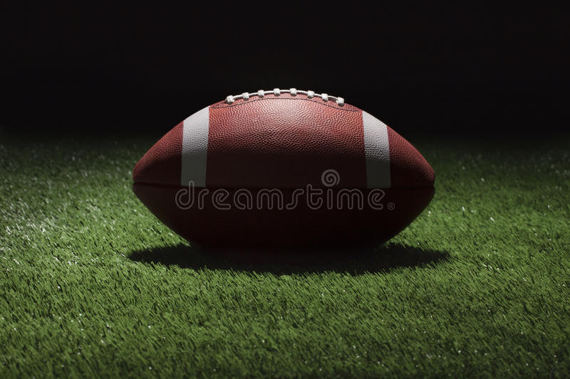 College football on grass field at night with spot lighting. College style football on grass field at night shot with spot lighting stock photo