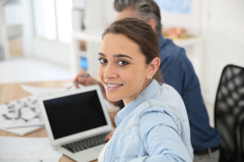 College girl in classroom using laptop. College girl in training course using laptop stock image