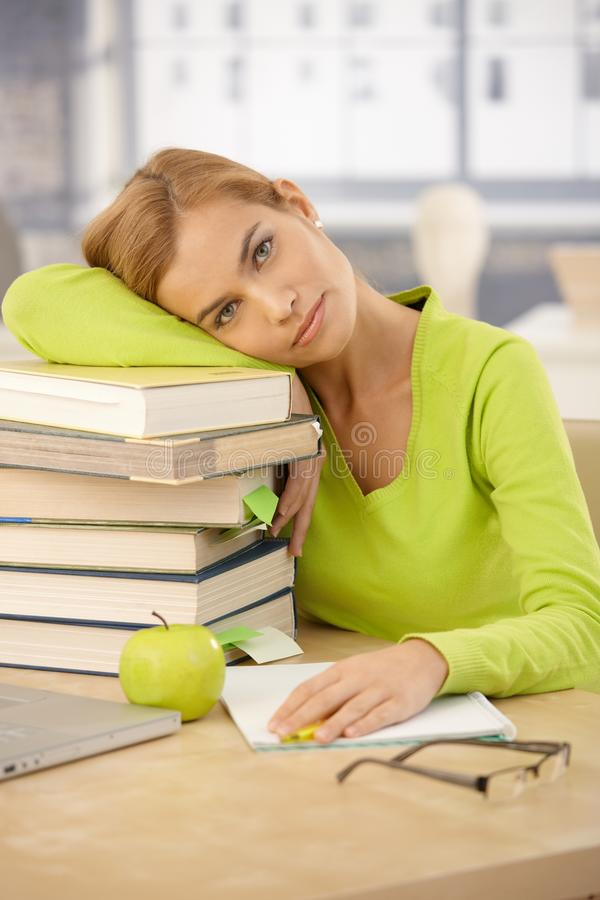 College girl relaxing with head on books. Portrait of tired college girl relaxing with head on books at desk, looking at camera royalty free stock images
