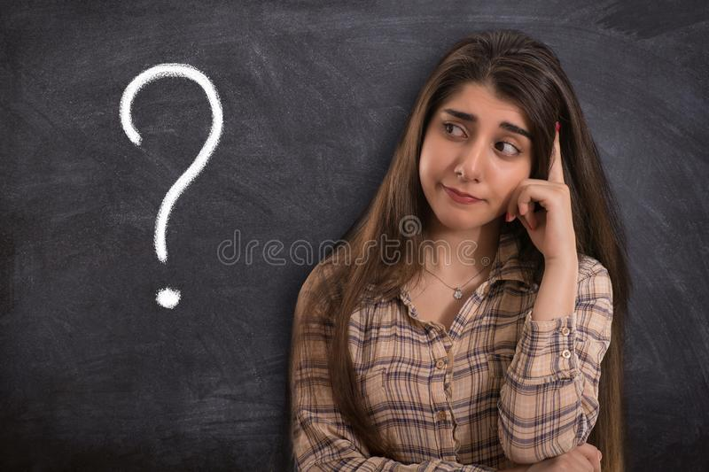 College girl thinking with question mark. Portrait of a beautiful young woman or college girl thinking front of blackboard with question mark royalty free stock photography