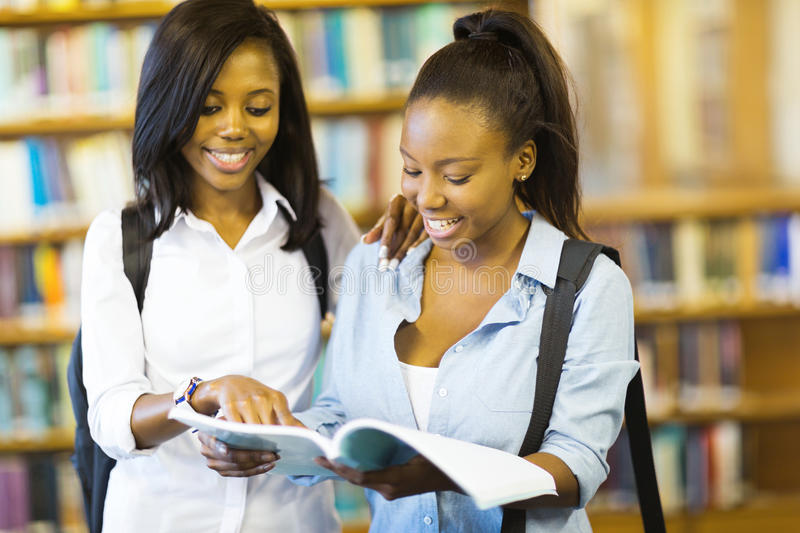 College girls reading book. Cheerful african college girls reading a book in library royalty free stock photography