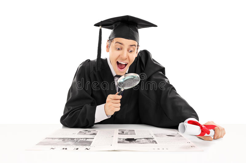 College graduate searching for job in newspaper stock photos