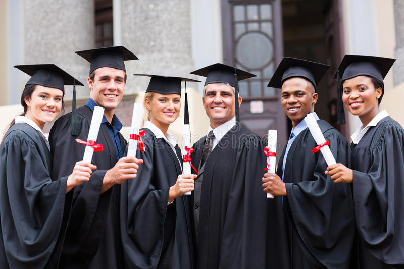 College graduates professor. Group of young college graduates and professor at graduation stock photos