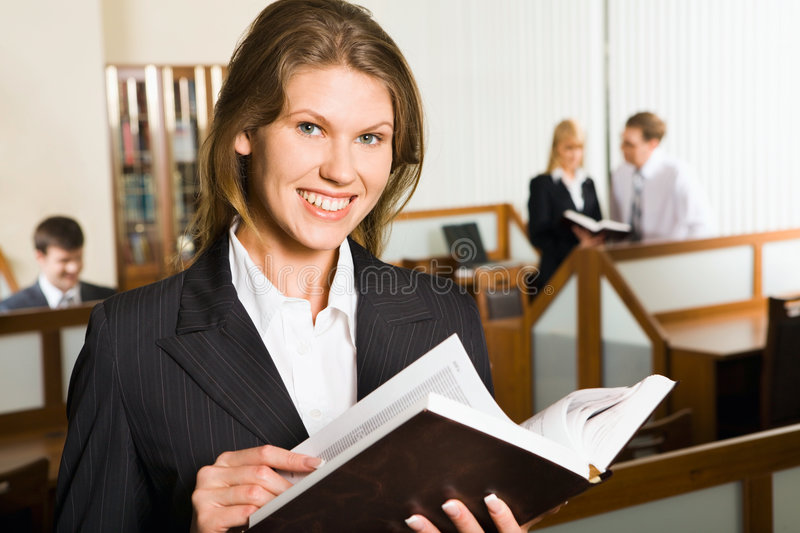 College library. Portrait of smiling young student holding thick opened book gazing at the camera and three Caucasian persons in different workplaces in the stock photo