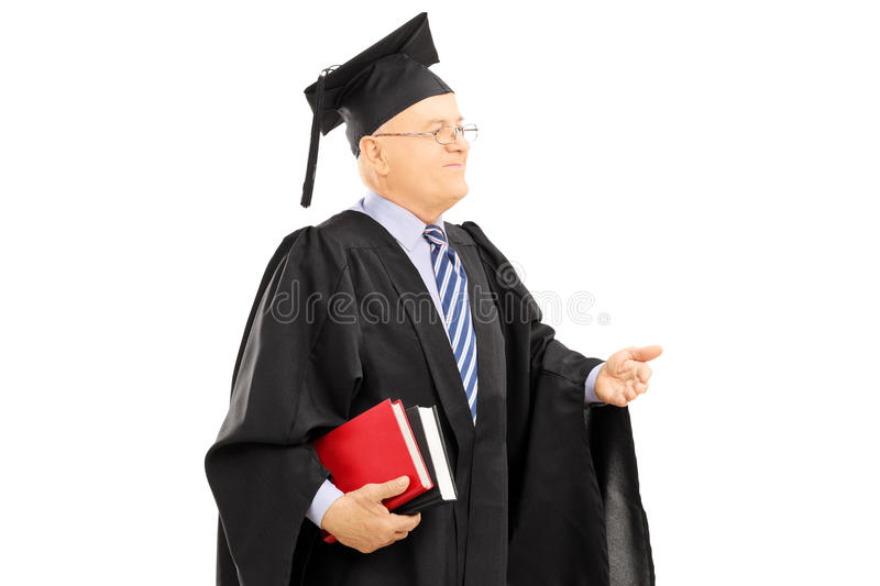 College professor in graduation gown holding book royalty free stock photography