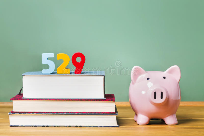 529 college savings plan theme with textbooks and piggy bank stock photography