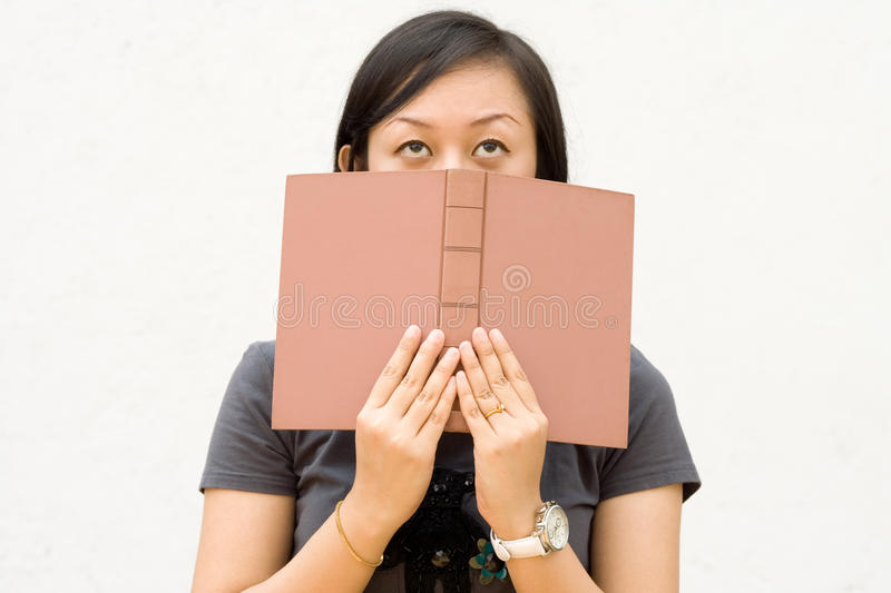 College student covering her face with book stock photography