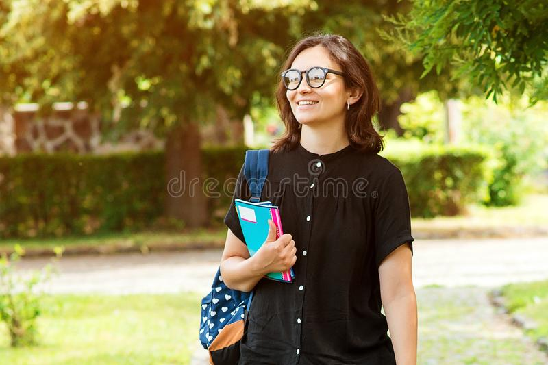 College student girl looking happy smiling outdoors. Student with book or notebook in campus park. Beautiful young woman in stock photography