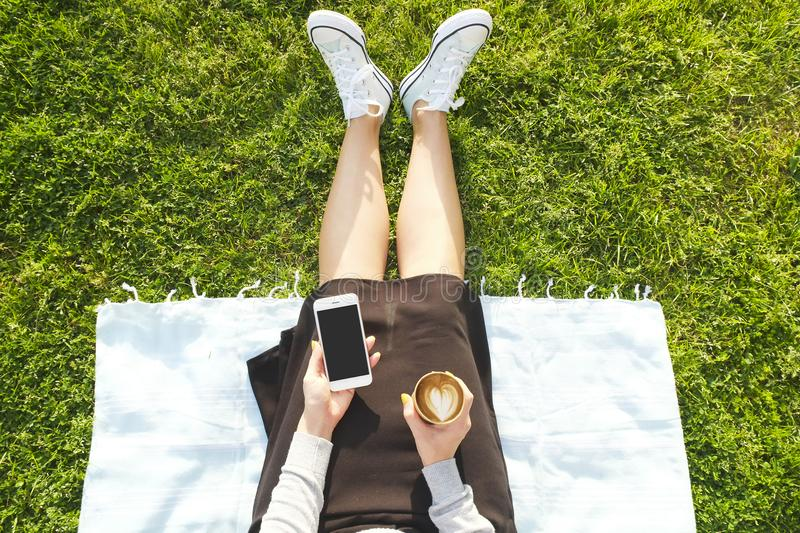 College student girl sitting on the green lawn messaging texting on her smartphone device. Young woman sitting at the park bloggin stock photography