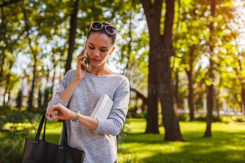 College student talking on mobile phone in park. Young woman holding book and checking time royalty free stock image