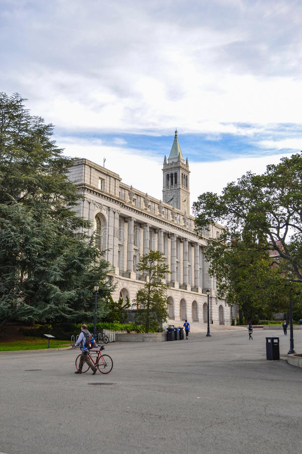 College Student Walking His Bike to Class. College student walks his bike to class at the University of California, Berkeley. The UC Berkeley campus is located royalty free stock images