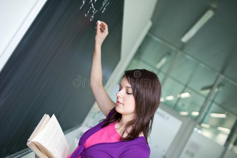 College student writing on the chalkboard. Pretty young college student writing on the chalkboard/blackboard during a math class royalty free stock photos