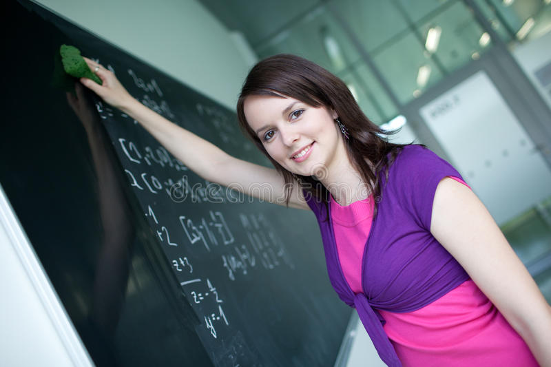 College student writing on the chalkboard. Pretty young college student writing on the chalkboard/blackboard during a math class royalty free stock images