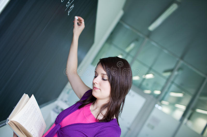 College student writing on the chalkboard. Pretty young college student writing on the chalkboard/blackboard during a math class stock photo