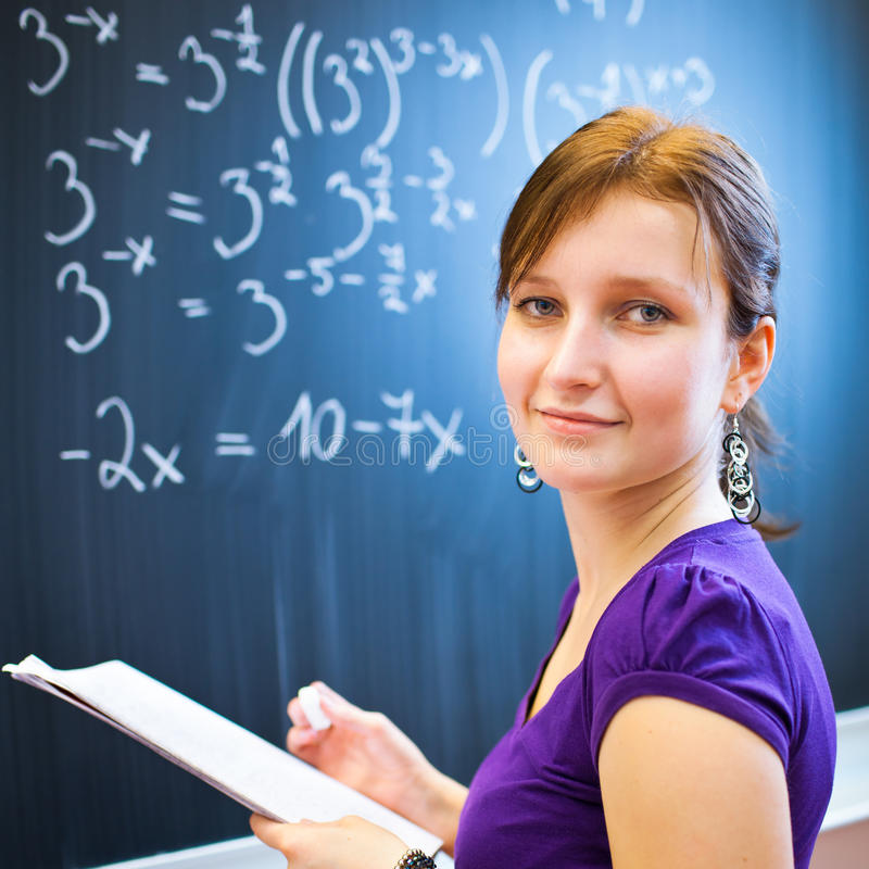 College student writing on the chalkboard. Pretty young college student writing on the chalkboard/blackboard during a math class (color toned image; shallow DOF royalty free stock photos