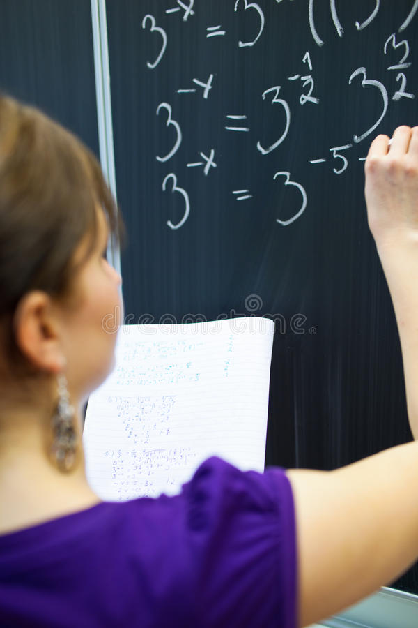College student writing on the chalkboard. Pretty young college student writing on the chalkboard/blackboard during a math class (color toned image; shallow DOF royalty free stock images
