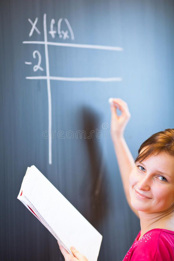 College student writing on the chalkboard. Pretty young college student writing on the chalkboard/blackboard during a math class (color toned image; shallow DOF royalty free stock photography