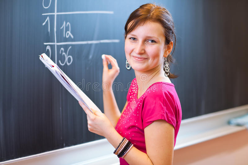 College student writing on the chalkboard. Pretty young college student writing on the chalkboard/blackboard during a math class (color toned image; shallow DOF stock photo