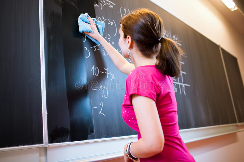 College student writing on the chalkboard. Pretty young college student writing on the chalkboard/blackboard during a math class (color toned image; shallow DOF royalty free stock photo