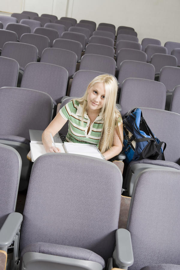 College Student Writing In Lecture Room stock photo