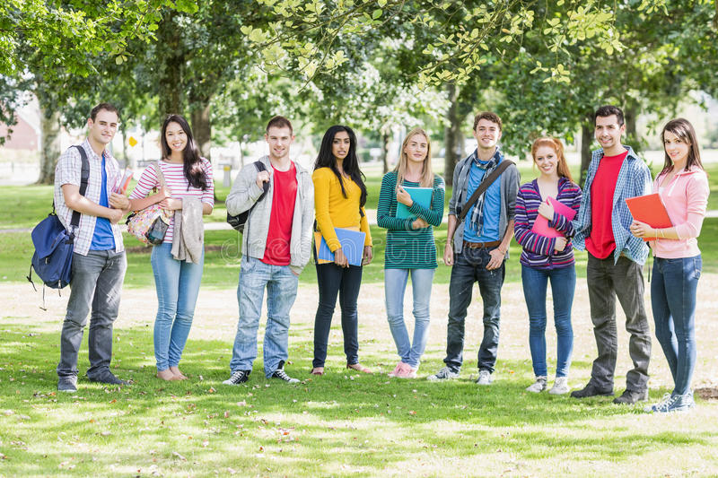 College students with bags and books standing in park royalty free stock image