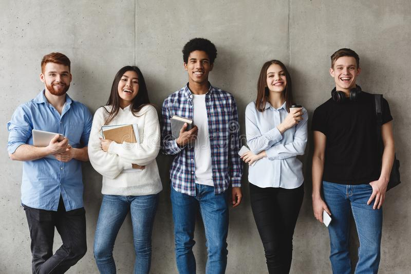 College students with books smiling to camera over grey wall stock image