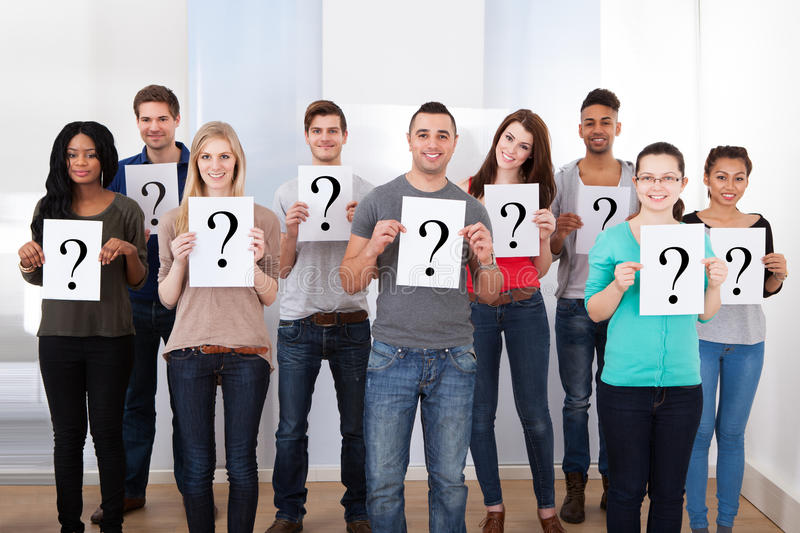 College students holding question mark signs. Group portrait of confident college students holding question mark signs in classroom stock photos