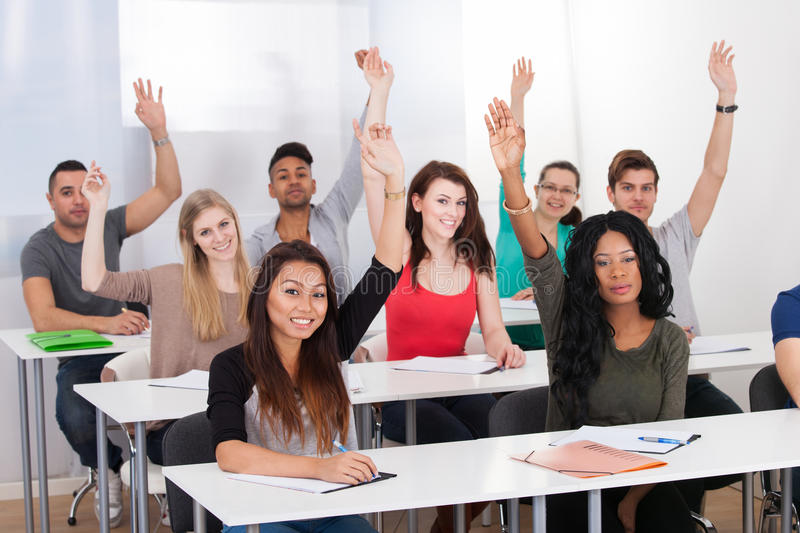 College Students Raising Hands In Classroom Stock Photo ...