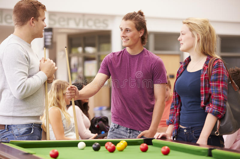 College Students Relaxing And Playing Pool Together royalty free stock image