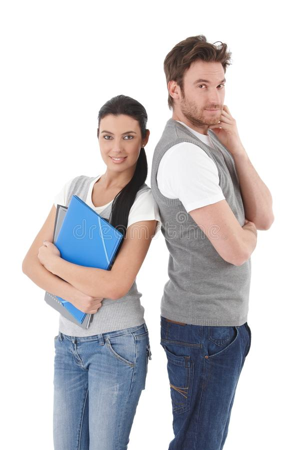 College students standing with back to each other. Smiling stock photography