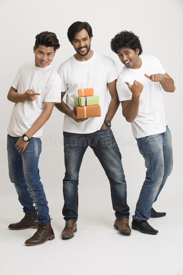 College students standing with gift boxes. Cheerful happy college students posing with gift boxes on white background stock photos
