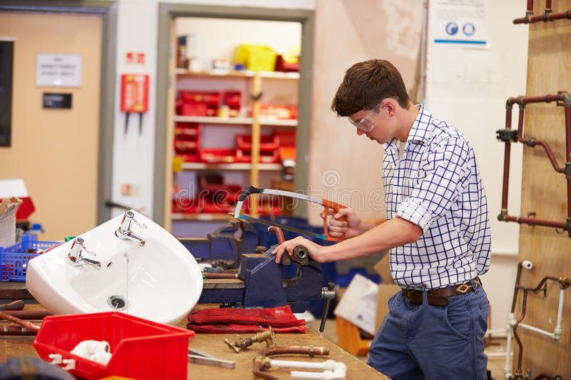 College Students Studying Plumbing Working At Bench royalty free stock image