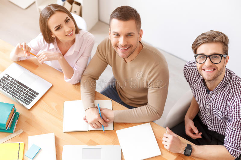 College students studying together at home. Improving their minds through education. Top view of smiling students looking at camera, preparing for exams at home stock photography