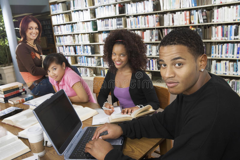 College Students Studying Together In Library. Group of multiethnic college students studying together in library stock image