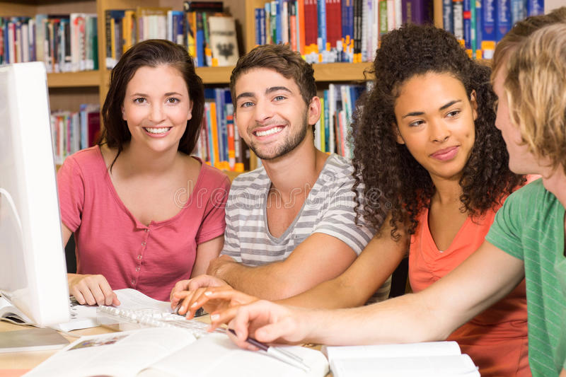 College students using computer in library. Group of college students using computer in the library royalty free stock image