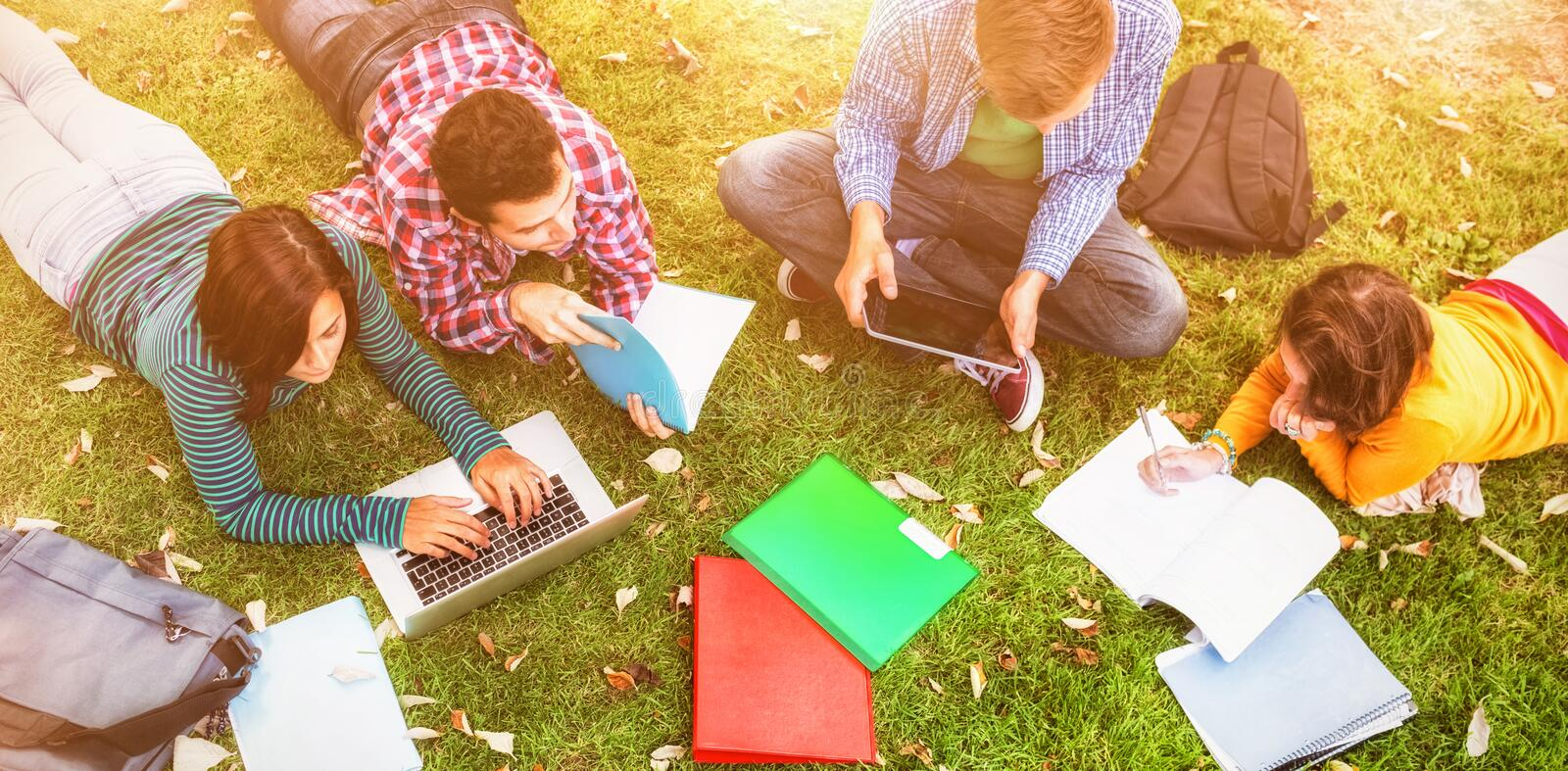 College students using laptop while doing homework. At park